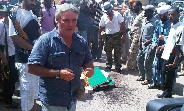 CNN's Ben Wedeman broadcasts live from Sabha while opposition fighters burn Gaddafi's green books